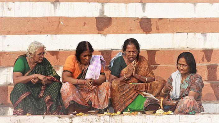 Donne in preghiera sui ghat in preghiera